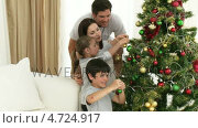 Купить «Young family decorating a Christmas tree together», видеоролик № 4724917, снято 22 июля 2019 г. (c) Wavebreak Media / Фотобанк Лори