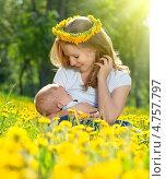 Купить «Мать кормит грудью своего ребенка на зеленом лугу с желтыми цветами», фото № 4757797, снято 3 июня 2013 г. (c) Евгений Атаманенко / Фотобанк Лори