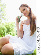 Купить «Девушка в платье и цветами в руках вдыхает их аромат, сидя на траве в парке», фото № 4763413, снято 17 ноября 2011 г. (c) Wavebreak Media / Фотобанк Лори