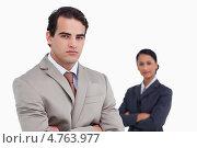 Купить «Деловой мужчина, сложив руки на груди, позирует на камеру. На заднем плане - деловая женщина», фото № 4763977, снято 8 ноября 2011 г. (c) Wavebreak Media / Фотобанк Лори