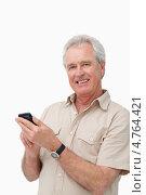 Купить «Улыбающийся пожилой мужчина разговаривает по мобильному телефону», фото № 4764421, снято 8 ноября 2011 г. (c) Wavebreak Media / Фотобанк Лори