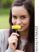 Купить «Молодая женщина улыбается, вдыхая аромат яркого цветка», фото № 4764621, снято 14 ноября 2011 г. (c) Wavebreak Media / Фотобанк Лори