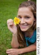 Купить «Красивая длинноволосая девушка вдыхает аромат цветка в руке, лежа на траве, и смеется», фото № 4767989, снято 14 ноября 2011 г. (c) Wavebreak Media / Фотобанк Лори