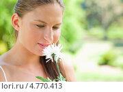 Купить «Симпатичная молодая женщина держит в руках цветы и вдыхает их аромат», фото № 4770413, снято 17 ноября 2011 г. (c) Wavebreak Media / Фотобанк Лори
