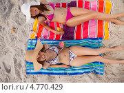 Купить «Привлекательные девушки лежат на полотенце на пляже с бокалами коктейлей в руках и улыбаются», фото № 4770429, снято 18 ноября 2011 г. (c) Wavebreak Media / Фотобанк Лори