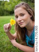 Купить «Симпатичная девушка вдыхает аромат цветка в руке, лежа на траве», фото № 4770905, снято 14 ноября 2011 г. (c) Wavebreak Media / Фотобанк Лори