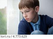 Грустный подросток смотрит в окно. Стоковое фото, фотограф Римма Зайцева / Фотобанк Лори