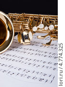 Купить «Саксофон лежит на музыкальных нотах, крупный план», фото № 4774325, снято 23 декабря 2012 г. (c) Андрей Попов / Фотобанк Лори
