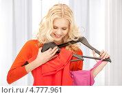 Купить «Юная девушка выбирает платье на вешалке», фото № 4777961, снято 2 октября 2011 г. (c) Syda Productions / Фотобанк Лори