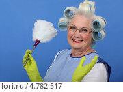 Купить «Улыбающаяся пожилая женщина в бигуди с щеткой для пыли на синем фоне», фото № 4782517, снято 10 февраля 2011 г. (c) Phovoir Images / Фотобанк Лори