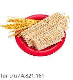 Купить «Зерновые хлебцы и колоски пшеница лежащие в красной тарелке изолированно на белом фоне», фото № 4821161, снято 10 апреля 2013 г. (c) Литвяк Игорь / Фотобанк Лори