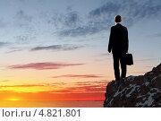 Бизнесмен с портфелем стоит на вершине горы и смотрит на закат. Стоковое фото, фотограф Sergey Nivens / Фотобанк Лори