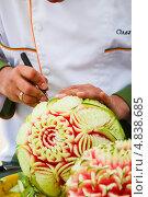 Ажурный арбуз, мужчина вырезает узоры из арбуза (2013 год). Редакционное фото, фотограф Екатерина Черняева / Фотобанк Лори