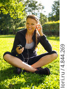Улыбающаяся молодая женщина слушает музыку с телефона, сидя на траве в парке. Стоковое фото, фотограф Andrejs Pidjass / Фотобанк Лори