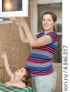 Купить «Беременная женщина разогревает продукты питания», фото № 4846017, снято 9 августа 2012 г. (c) Яков Филимонов / Фотобанк Лори