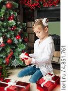 Купить «Девочка открывает подарочную коробку около новогодней елки», фото № 4851761, снято 4 ноября 2012 г. (c) Оксана Гильман / Фотобанк Лори