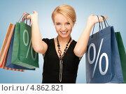 Купить «Счастливая молодая женщина с пакетами, на которых указан знак процентов», фото № 4862821, снято 12 февраля 2011 г. (c) Syda Productions / Фотобанк Лори