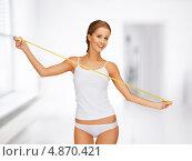 Купить «Красивая стройная девушка с лентой сантиметра в руках измеряет объемы своего тела», фото № 4870421, снято 16 сентября 2012 г. (c) Syda Productions / Фотобанк Лори