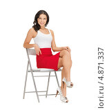 Купить «Красивая брюнетка в красной юбке сидит на стуле на белом фоне», фото № 4871337, снято 12 апреля 2012 г. (c) Syda Productions / Фотобанк Лори
