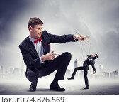 Купить «Бизнесмен-марионетка танцует в руках кукловода», фото № 4876569, снято 25 мая 2018 г. (c) Sergey Nivens / Фотобанк Лори