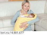 Мама сидит на полу с малышом в руках. Стоковое фото, агентство Wavebreak Media / Фотобанк Лори