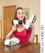 Купить «Длинноволосая женщина сушит кроссовки феном», фото № 4892761, снято 26 мая 2013 г. (c) Яков Филимонов / Фотобанк Лори