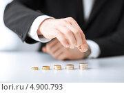 Купить «Мужчина раскладывает монеты на столе», фото № 4900793, снято 22 марта 2013 г. (c) Syda Productions / Фотобанк Лори