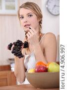 Купить «Девушка ест виноград рядом с миской с фруктами», фото № 4906997, снято 13 января 2011 г. (c) Phovoir Images / Фотобанк Лори