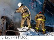 Два сотрудника МЧС России тушат пожар (2013 год). Редакционное фото, фотограф Литвяк Игорь / Фотобанк Лори