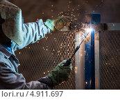 Купить «Электросварщик в защитной маске сваривает металлоконструкцию», фото № 4911697, снято 21 июля 2013 г. (c) Илья Андриянов / Фотобанк Лори