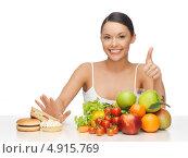 Купить «Красивая молодая женщина отказывается от вредной еды в пользу овощей и фруктов», фото № 4915769, снято 12 января 2013 г. (c) Syda Productions / Фотобанк Лори