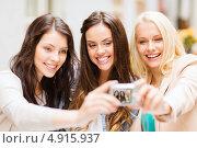 Купить «Красивые молодые подруги сидят в уличном кафе и фотографируются», фото № 4915937, снято 29 июня 2013 г. (c) Syda Productions / Фотобанк Лори
