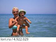 Женщина с маленьким смеющимся ребенком на фоне голубого моря. Фокус на малыше. Стоковое фото, фотограф Роман Кокорев / Фотобанк Лори