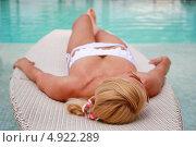 Женщина загорает лежа на шезлонге у бассейна с морской водой. Стоковое фото, фотограф Роман Кокорев / Фотобанк Лори