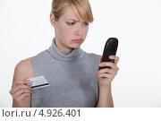 Недовольная девушка с кредитной картой и телефонной трубкой. Стоковое фото, фотограф Phovoir Images / Фотобанк Лори