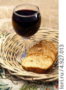 Купить «Плетеная тарелка с хлебом и бокал красного вина», фото № 4927013, снято 30 июля 2013 г. (c) ElenArt / Фотобанк Лори