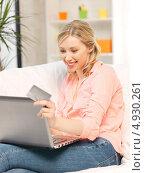 Купить «Красивая молодая женщина с кредитной картой и ноутбуком дома на диване», фото № 4930261, снято 17 июня 2012 г. (c) Syda Productions / Фотобанк Лори