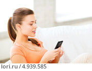 Купить «Юная девушка дома с современным смартфоном в руках», фото № 4939585, снято 1 июня 2013 г. (c) Syda Productions / Фотобанк Лори