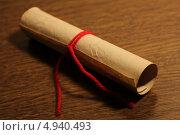 Старый старинный свиток, перевязанный красной ниткой, лежит на столе. Стоковое фото, фотограф Ольга / Фотобанк Лори