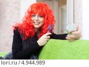 Купить «Улыбающаяся девушка в красном парике смотрится в зеркало», фото № 4944989, снято 21 декабря 2012 г. (c) Яков Филимонов / Фотобанк Лори