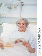 Купить «Пожилая пациентка в больничной койке с журналом», фото № 4948697, снято 25 апреля 2012 г. (c) Wavebreak Media / Фотобанк Лори