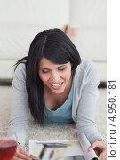 Купить «Улыбающаяся брюнетка лежит на животе на полу с открытым журналом», фото № 4950181, снято 29 марта 2012 г. (c) Wavebreak Media / Фотобанк Лори