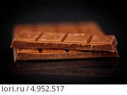 Плитка шоколада с отломанными четырьмя дольками. Стоковое фото, агентство Wavebreak Media / Фотобанк Лори
