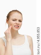 Купить «Сморщившись от боли, девушка массирует себе челюсть», фото № 4955853, снято 5 апреля 2012 г. (c) Wavebreak Media / Фотобанк Лори