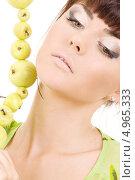 Купить «Молодая брюнетка с зелеными яблоками на нитке», фото № 4965333, снято 25 октября 2008 г. (c) Syda Productions / Фотобанк Лори