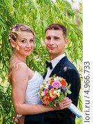 Купить «Красивые жених и невеста среди зелёной листвы на прогулке», эксклюзивное фото № 4966733, снято 15 июня 2013 г. (c) Игорь Низов / Фотобанк Лори
