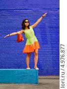 Девушка в легком ярком платье стоит на фоне синей стены с раскинутыми в стороны руками. Стоковое фото, фотограф Юрий Селиванов / Фотобанк Лори