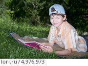 Мальчик-подросток лежит на траве с книгой. Стоковое фото, фотограф Сергей Видинеев / Фотобанк Лори