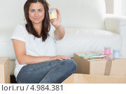 Купить «Брюнетка держит в руках желтый колер, сидя на ковре среди картонных коробок», фото № 4984381, снято 4 июля 2012 г. (c) Wavebreak Media / Фотобанк Лори