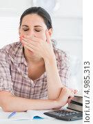 Купить «Уставшая брюнетка в клетчатой рубашке зевает, сидя за рабочим столом», фото № 4985313, снято 31 мая 2012 г. (c) Wavebreak Media / Фотобанк Лори